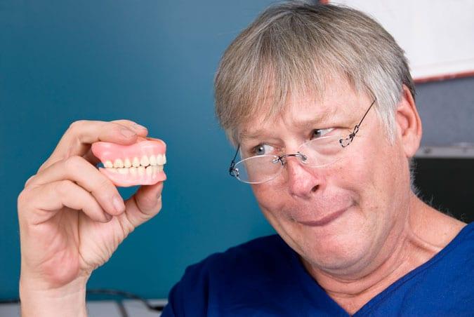 hombre mayor con dentadura postiza en la mano