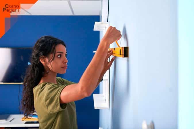 mujer pegar fotos en la pared sin dejar marca